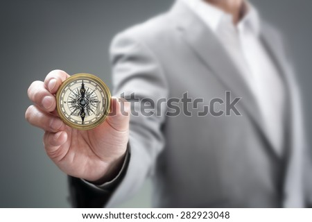 Businessman holding compass showing direction concept for guidance, strategy and business orientation - stock photo