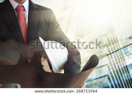 Businessman holding construction helmet and blueprints - stock photo