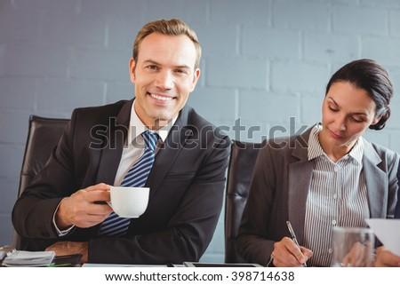 Businessman holding cup and smiling at camera and his colleague working beside him - stock photo