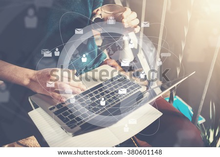 Businessman holding cup of coffee in hand and working with laptop. Generic design laptop on his knees. Digital interface effect. Horizontal mockup - stock photo