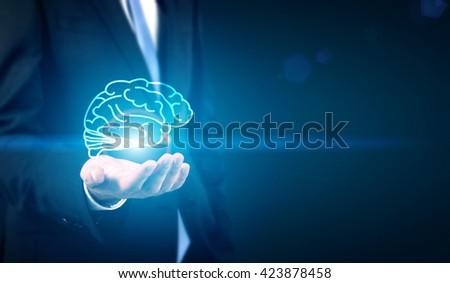 Businessman holding digital brain image in palm - stock photo
