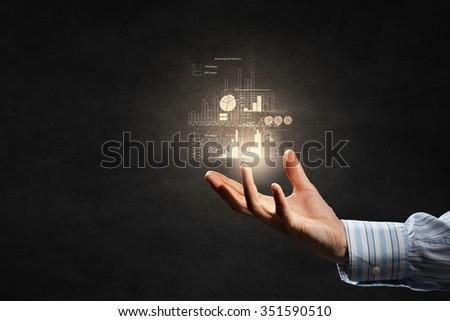 Businessman holding digital image of infographs in hand