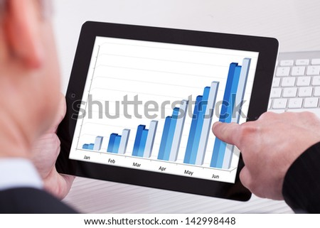 Businessman Holding Digital Tablet Showing Growth Graph