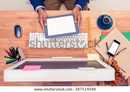 Businessman holding digital tablet while sitting at computer desk in creative office - stock photo