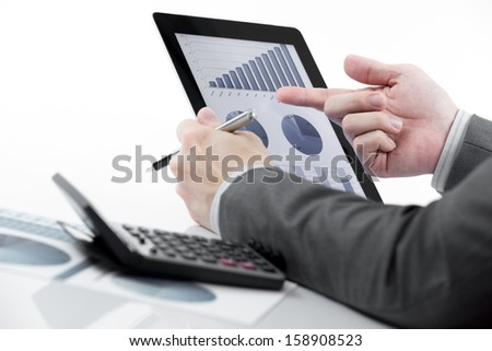 Businessman holding digital tablet with business report