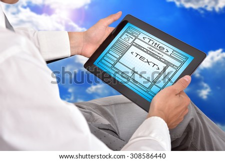 businessman holding digital tablet with template website