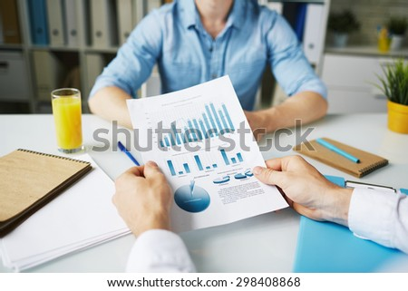 Businessman holding document with data in working environment