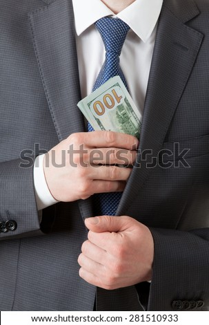 Businessman holding dollars/putting dollars in a pocket, closeup shot
