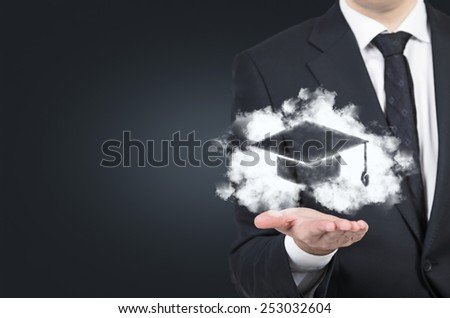businessman holding drawing bachelor hat on black background - stock photo