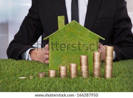 Businessman Holding Eco Friendly House In Front Of Stack Of Coins Over Grass - stock photo