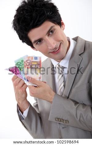 Businessman holding Euro bank notes - stock photo