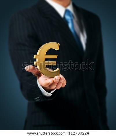 Businessman holding euro sign - stock photo