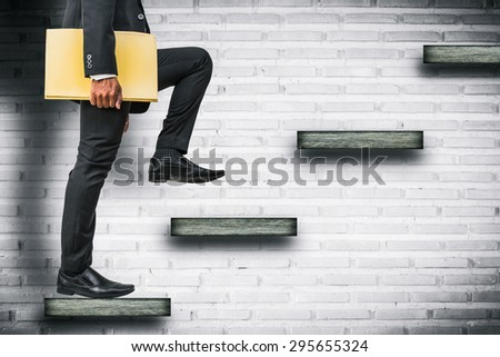 businessman holding files climbing stairs on brick wall - stock photo