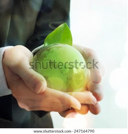 Businessman holding glass globus - stock photo
