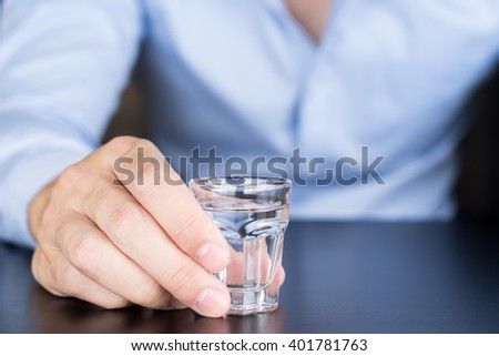 Businessman holding glass of vodka