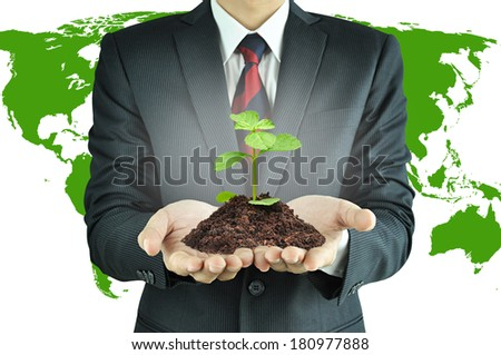 Businessman holding green seedling with soil - sustainable development & conservation concept - stock photo