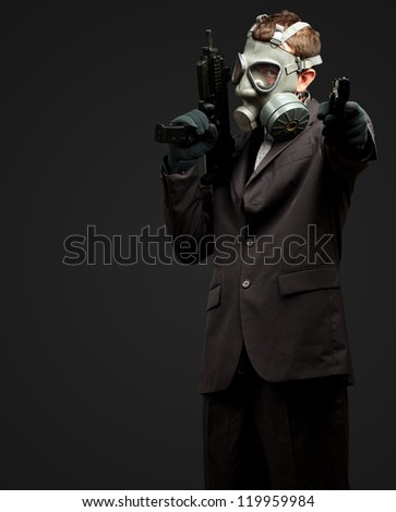 Businessman Holding Gun With Gas Mask against a black background
