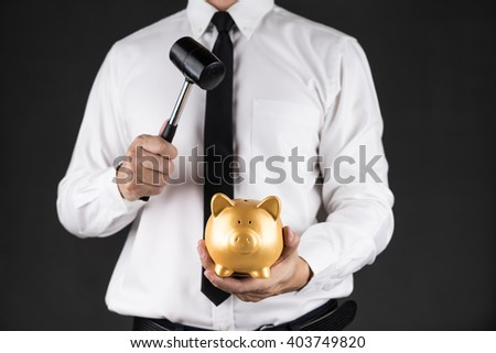 Businessman holding hammer and Gold piggy bank for saving - stock photo