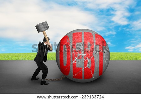 businessman holding hammer hitting cracked DEBT ball with nature sky clouds background - stock photo