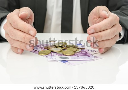 Businessman holding hand around Euro money as if giving it power and energy. Concept of help and solution for recession. - stock photo