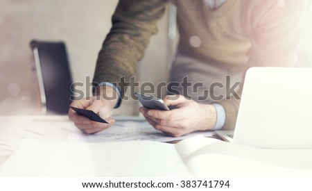 Businessman holding hand businesscard and making photo smartphone. Architectural project on the table. Horizontal mockup. Blurred, bokeh effect