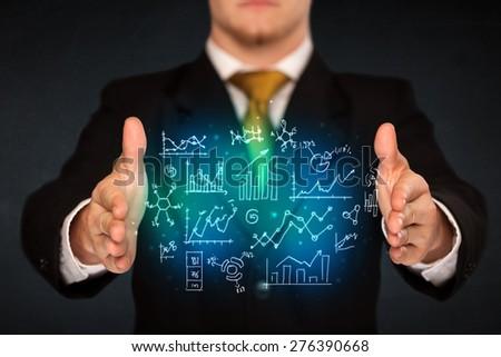 Businessman holding hand drawn business schemes - stock photo