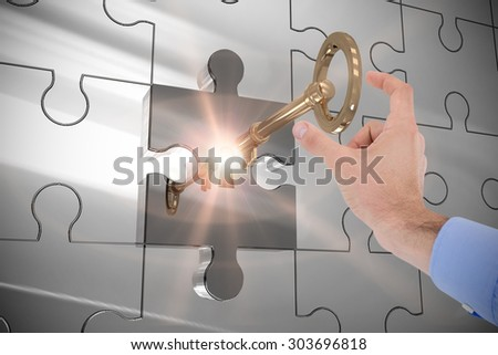 Businessman holding hand out in presentation against key unlocking jigsaw - stock photo