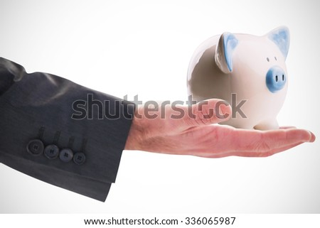 Businessman holding hand out in presentation against piggy bank