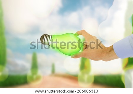 Businessman holding hand out in presentation against road leading out to the horizon - stock photo