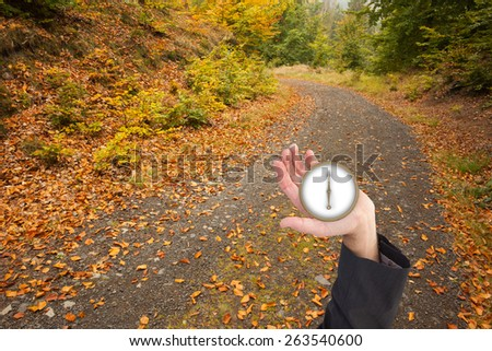 businessman holding hand out in presentation in the forest - stock photo