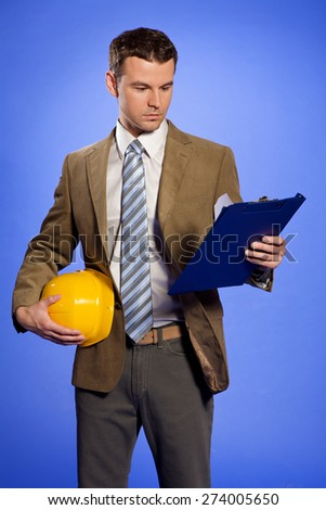 Businessman holding hardhat and looking at clipboard - stock photo