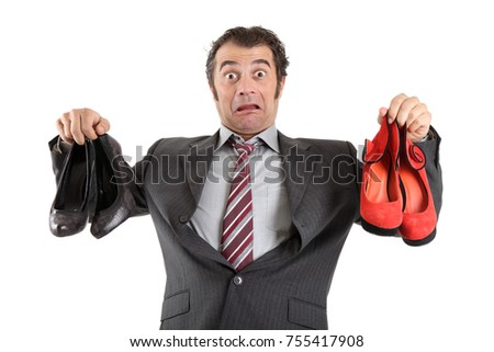 Businessman holding high heel shoes in front of white background