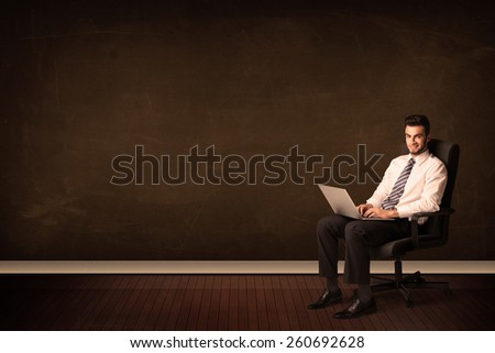 Businessman holding high tech laptop on brown background with copyspace - stock photo