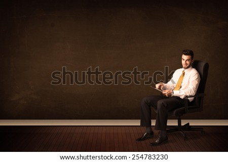 Businessman holding high tech tablet on brown background with copyspace - stock photo