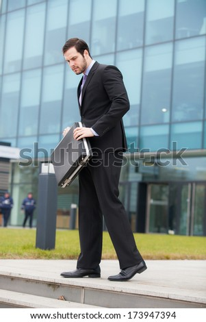 businessman holding his briefcase in his hands in front of an office building - stock photo