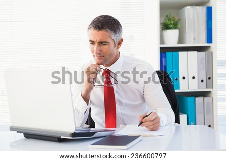 Businessman holding his glasses and take notes in his office