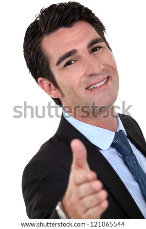 Businessman holding his hand out for a handshake - stock photo