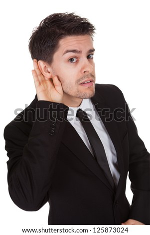 Businessman holding his hand to his ear isolated on white - stock photo