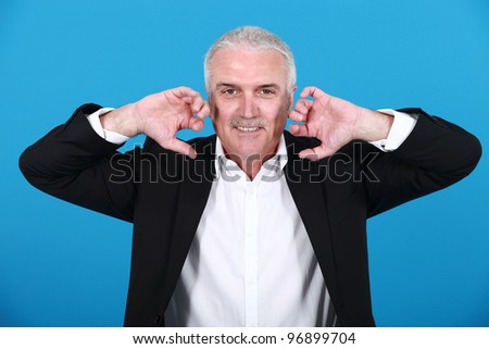 businessman holding his hands close to his ears - stock photo