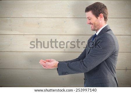 Businessman holding his hands out against bleached wooden planks background