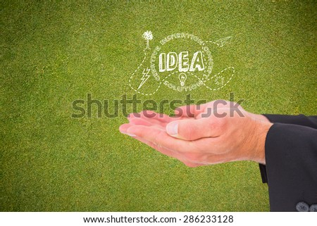 Businessman holding his hands out against green background - stock photo