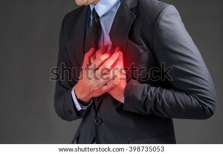 Businessman holding his heart in pain