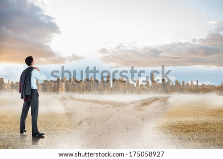 Businessman holding his jacket against path in yellow field leading to city