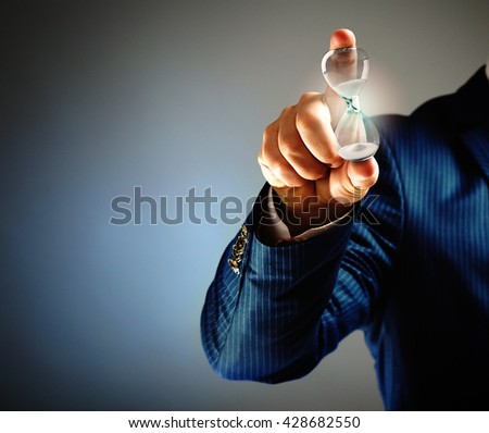 Businessman holding hourglass in hand on grey background - stock photo