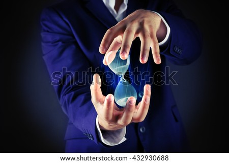 Businessman holding hourglass in hands on dark background - stock photo
