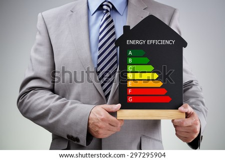 Businessman holding house shape blackboard with chalk energy efficiency rating chart concept for performance, efficiency and environmental conservation - stock photo