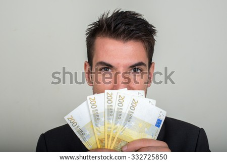 Businessman holding in hands 200 euros - stock photo