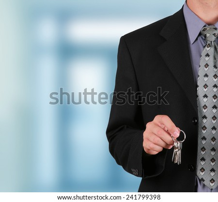 Businessman holding key in his hand to hand it over                             - stock photo