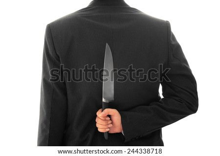 Businessman Holding Knife Behind His Back conceptual image Isolated - stock photo
