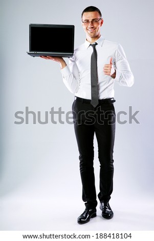 Businessman holding laptop and showing thumb up over gray background - stock photo